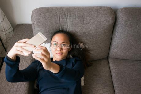 Sweden, Woman using smart phone on sofaの写真素材 [FYI02211734]
