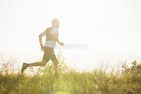 Man running through a field in Akersberga, Swedenの写真素材 [FYI02211746]