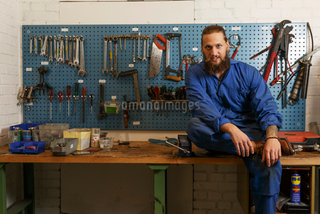 Mechanic sittings on a work bench in Swedenの写真素材 [FYI02211751]