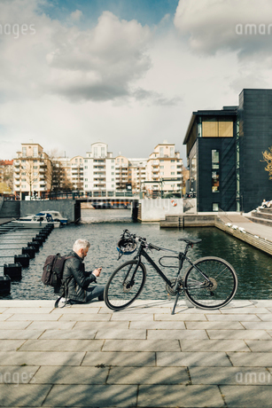 Man on smart phone with bicycle in Stockholm, Swedenの写真素材 [FYI02211756]