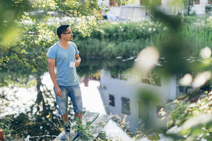 Mid adult man standing next to a river in Mortfors, Swedenの写真素材 [FYI02211823]