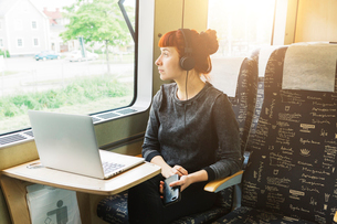 Woman using laptop on trainの写真素材 [FYI02211830]