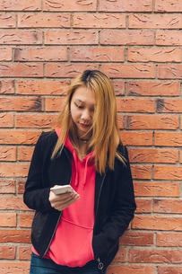 Teenage girl leaning on a brick wall looking at a cell phone in Swedenの写真素材 [FYI02211850]