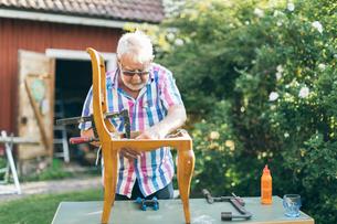 Senior man repairing a chair outdoors in Kvarnstugan, Swedenの写真素材 [FYI02211870]