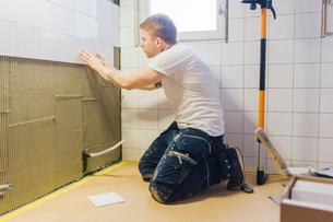 Man tiling a wallの写真素材 [FYI02211876]