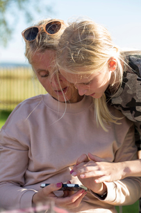 Mother and daughter looking at a cell phone outdoors in Swedenの写真素材 [FYI02211906]