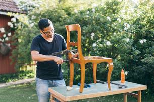 Mid adult man repairing a chair outdoors in Kvarnstugan, Swedenの写真素材 [FYI02211935]