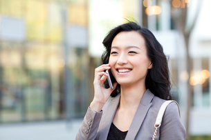 Cheerful young woman talking on the phone in cityの写真素材 [FYI02212030]