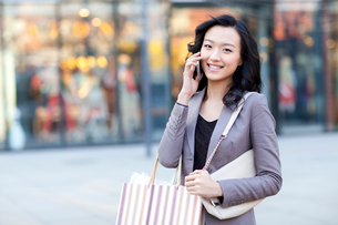 Cheerful young woman with shopping bags talking on the phoneの写真素材 [FYI02212074]