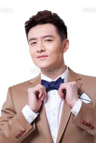 Stylish businessman adjusting bow tieの写真素材 [FYI02212195]