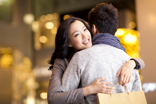 Sweet young couple embracing with shopping bag in handsの写真素材 [FYI02212312]