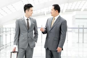 Business associates having conversation in airport lobbyの写真素材 [FYI02212372]