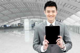 Young businessman showing digital tablet  at the airportの写真素材 [FYI02212378]