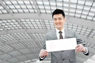 Chinese businessman holding blank sign in airport lobbyの写真素材 [FYI02212422]