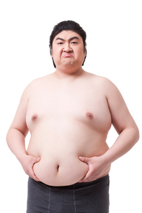 Funny obese man holding his pot bellyの写真素材 [FYI02212463]