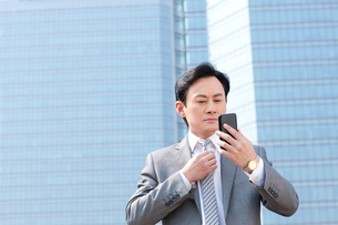 Serious businessman adjusting tie by reflection of mobile phの写真素材 [FYI02212504]