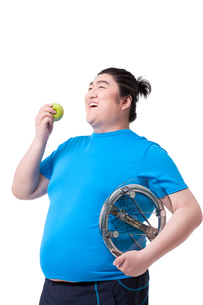 Cheerful fat man with apple and bathroom scaleの写真素材 [FYI02212565]
