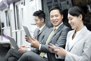Business persons using digital products in subway trainの写真素材 [FYI02212640]