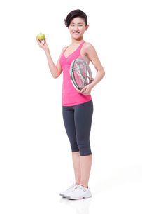 Slim young woman with apple and bathroom scaleの写真素材 [FYI02212672]