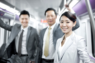 Cheerful businesswoman with partners in subway trainの写真素材 [FYI02212715]