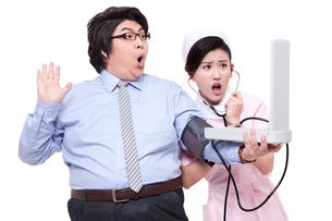 Nurse measuring blood pressure for overweight businessmanの写真素材 [FYI02212809]