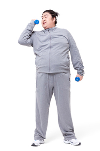 Overweight man exercising with dumbbellの写真素材 [FYI02212893]