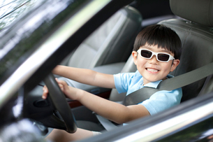 Excited boy pretending to drive carの写真素材 [FYI02212934]