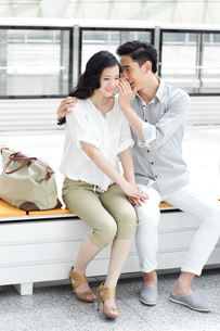 Young couple talking in secret at subway stationの写真素材 [FYI02212941]