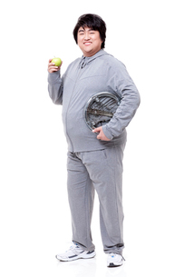 Overweight man with apple and scaleの写真素材 [FYI02212942]