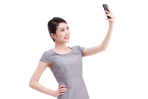 Young businesswoman photographs with mobile phoneの写真素材 [FYI02212947]