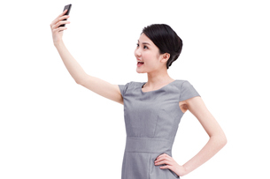Young businesswoman photographs with mobile phoneの写真素材 [FYI02212965]