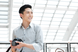 Young man with SLR camera at subway stationの写真素材 [FYI02213037]