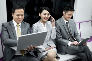 Business persons using digital products in subway trainの写真素材 [FYI02213104]
