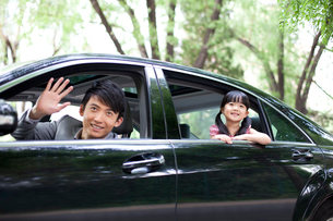 Cheerful father and daughter waving out of car windowの写真素材 [FYI02213105]