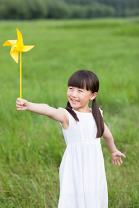 Happy girl playing paper windmill in the open airの写真素材 [FYI02213127]