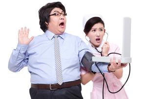 Nurse measuring blood pressure for overweight businessmanの写真素材 [FYI02213141]