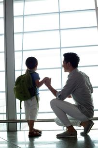 Father and son looking at view at the airportの写真素材 [FYI02213148]