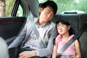 Father and daughter sleeping soundly in car back seatの写真素材 [FYI02213158]
