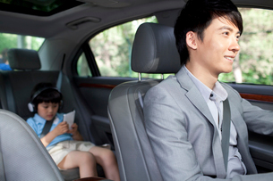 Cheerful father driving with son in back seatの写真素材 [FYI02213162]