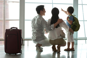 Young family looking at view at the airportの写真素材 [FYI02213219]