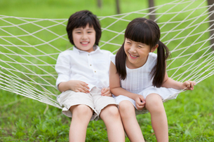 Excited children sitting in a hammock outdoorsの写真素材 [FYI02213241]
