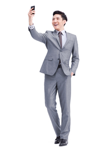 Young businessman photographs with mobile phoneの写真素材 [FYI02213245]