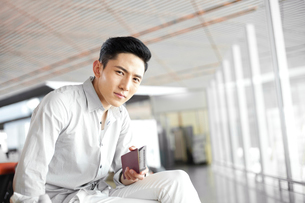 Young man waiting in airport lounge with flight ticket and pの写真素材 [FYI02213256]