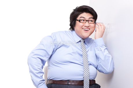 Overweight businessman doing eavesdroppingの写真素材 [FYI02213259]