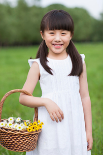Cute girl on the grass with basket of wildflowersの写真素材 [FYI02213278]