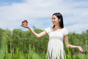 Young woman with toy houseの写真素材 [FYI02213338]