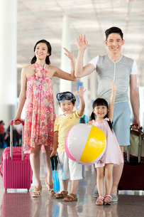 Cheerful family waving at the airportの写真素材 [FYI02213361]