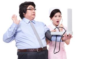 Nurse measuring blood pressure for overweight businessmanの写真素材 [FYI02213374]