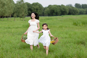 Excited mother and daughter running on the grassの写真素材 [FYI02213376]