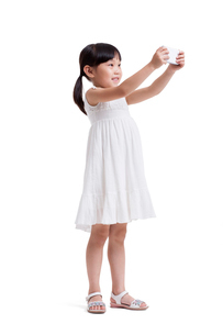 Cute little girl taking pictures with smart phoneの写真素材 [FYI02213405]